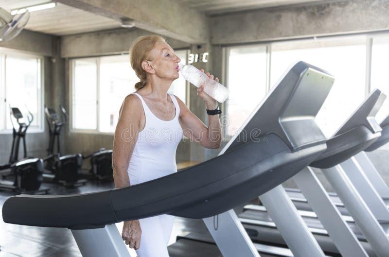 Durstiges Trinkwasser und Übung der älteren Frau, die an der Turnhalleneignung rüttelt ?lterer gesunder Lebensstil lizenzfreies stockfoto