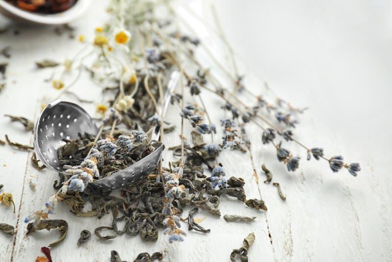 Durszlak z wysuszonymi herbacianymi liśćmi i lawendą na białym drewnianym stole zdjęcia stock
