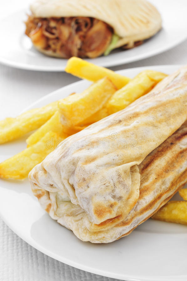Durum and doner kebab. Closeup of a durum kebab with fries and a doner kebab in the background on a set table stock photo