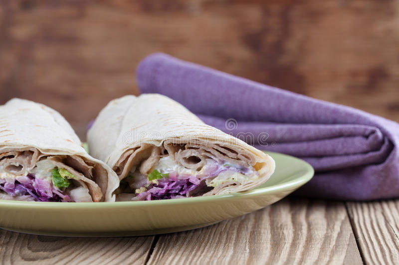 Durum kebab. Tortilla wraps with kebab, tzatziki and fresh salad royalty free stock photo