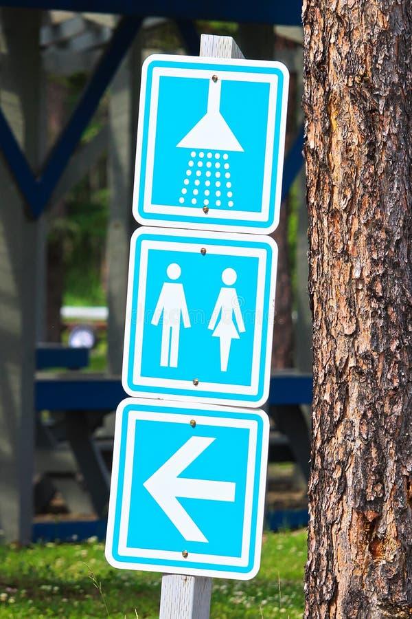 Duschar och ett toalettriktningstecken på en tältplats royaltyfri foto