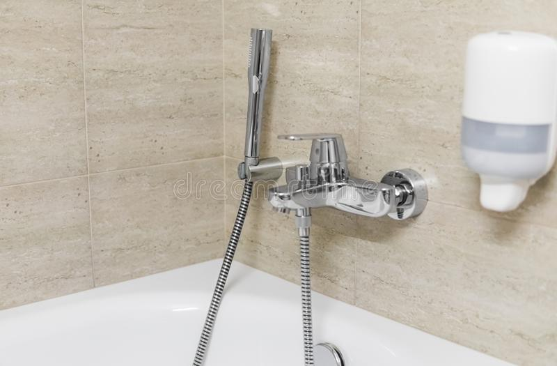 Dusche und Wannenmischer in einem Badezimmer stockbilder