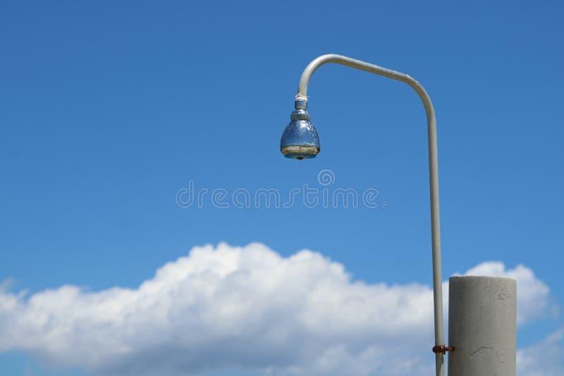 Duschender Duschkopf im Freien gegen blauen Himmel mit Wolken am Strand stockfotos