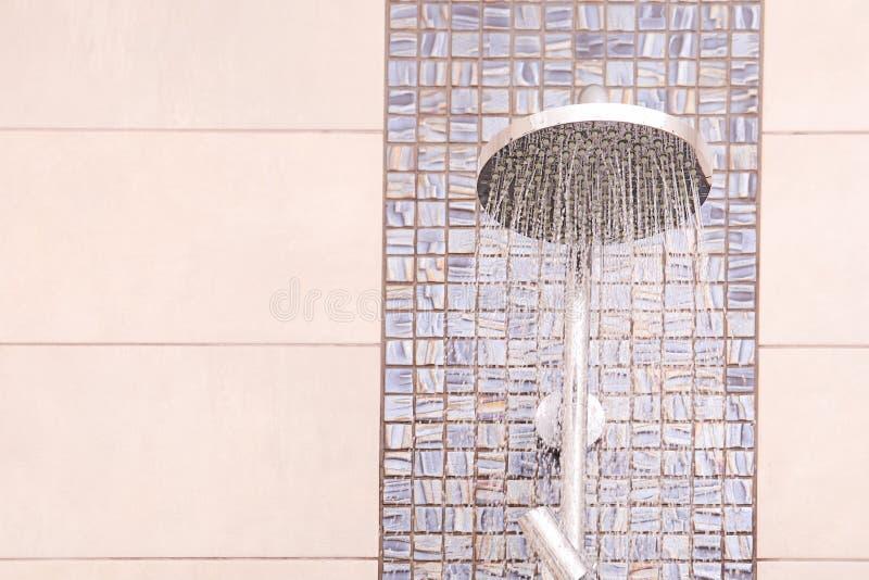 Duschhuvud med rinnande vatten i badrummet för text royaltyfria bilder