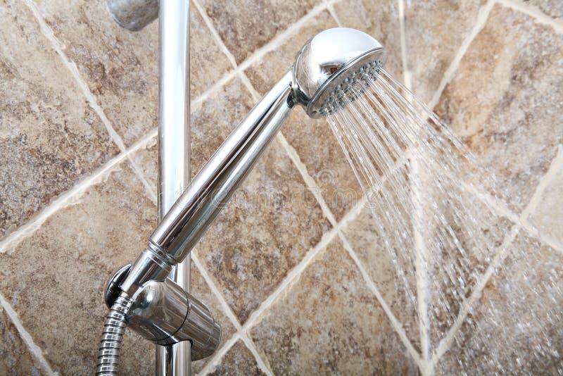Duschhuvud med rinnande vatten i ett badrum arkivbild