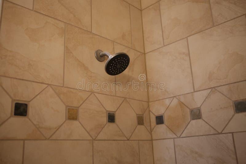 Duschkopf auf Fliesenwand im Badewannenbereich lizenzfreie stockfotos
