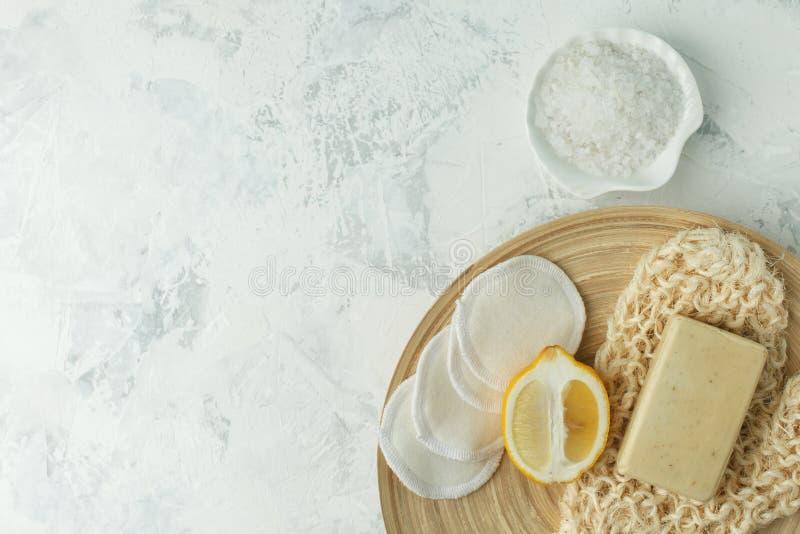 Duschtillbehör - massageborsten, svampen, citronen, havet saltar, tvål på en ljus bakgrund, bästa sikt Att rentvå av huden, skura royaltyfria foton