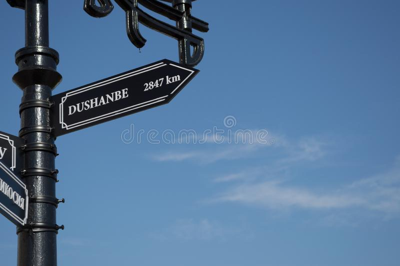 Dushanbe, Tajikistan, Asia. Pointer cities on the post. Blue sky on the background. White font on black stock photos