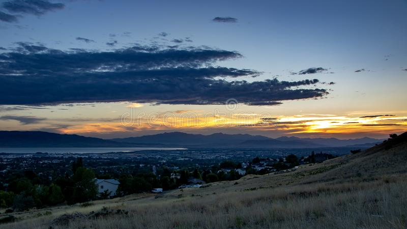 Dusk falls over a sleepy city in a valley with mountains and a lake in the background royalty free stock image