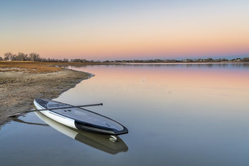 Dusk over lake with a paddleboard. Dusk over lake in Colorado with a stand up paddleboard on a beach stock photography