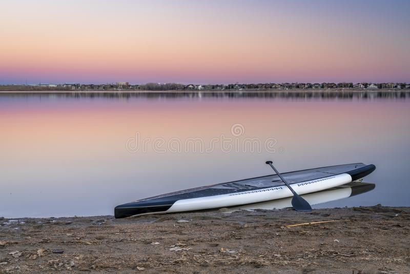 Dusk over lake with a paddleboard. Dusk over lake in Colorado with a stand up paddleboard on a beach royalty free stock photos