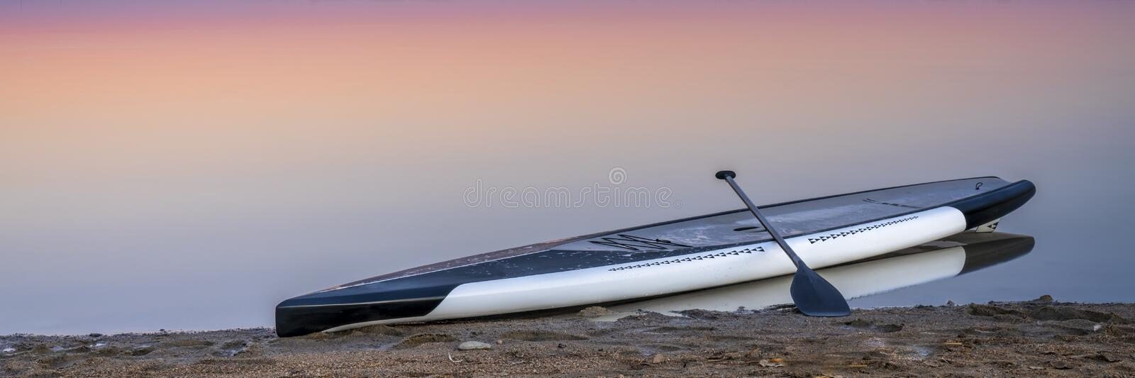 Dusk over lake with a paddleboard. Stand up paddleboard on a lake beach at dusk, panoramic banner royalty free stock images
