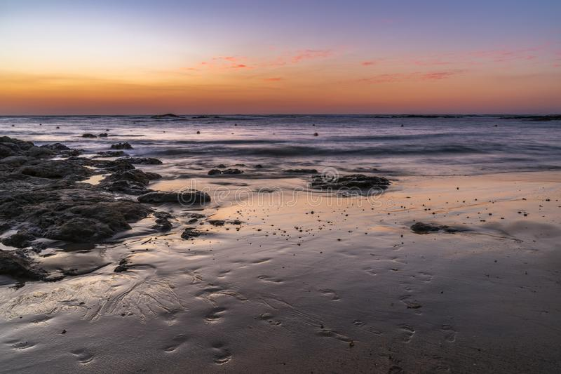 Dusk over the ocean with orange and purple sky reflecting on the beach. Dusk over the ocean with orange and purple sky reflecting on the sand with rocky area stock image