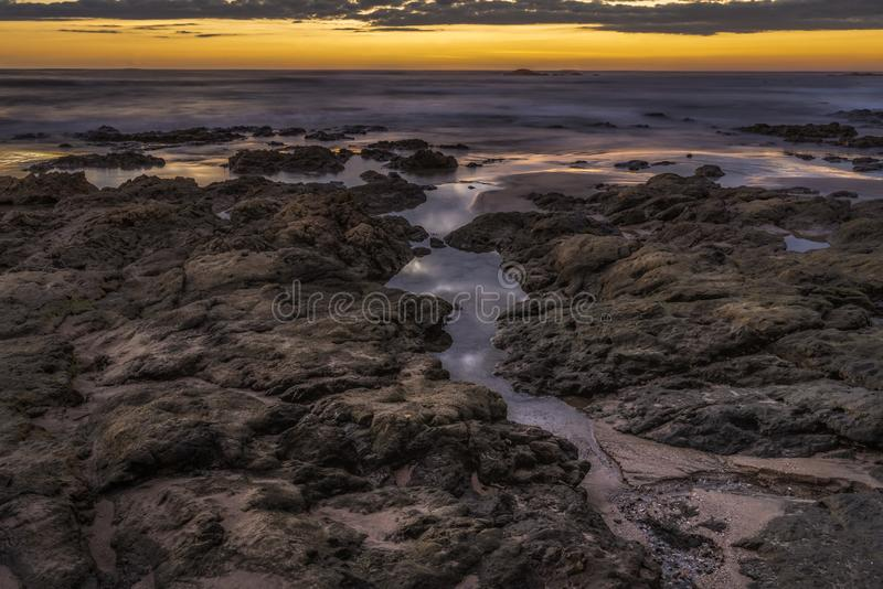 Dusk over the ocean with purple and golden sky. Along the rock coastline stock image