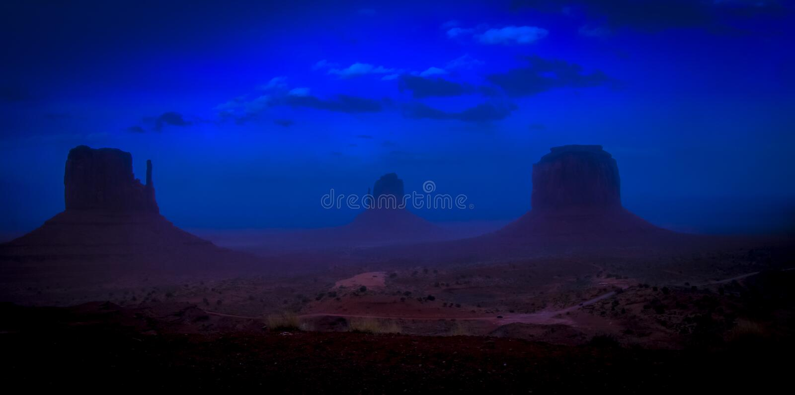 Monument Valley at dusk with iconic West and East Mitten Buttes, Arizona USA. At dusk, the red mesas and buttes of Monument Valley Navajo Tribal Park and the royalty free stock image