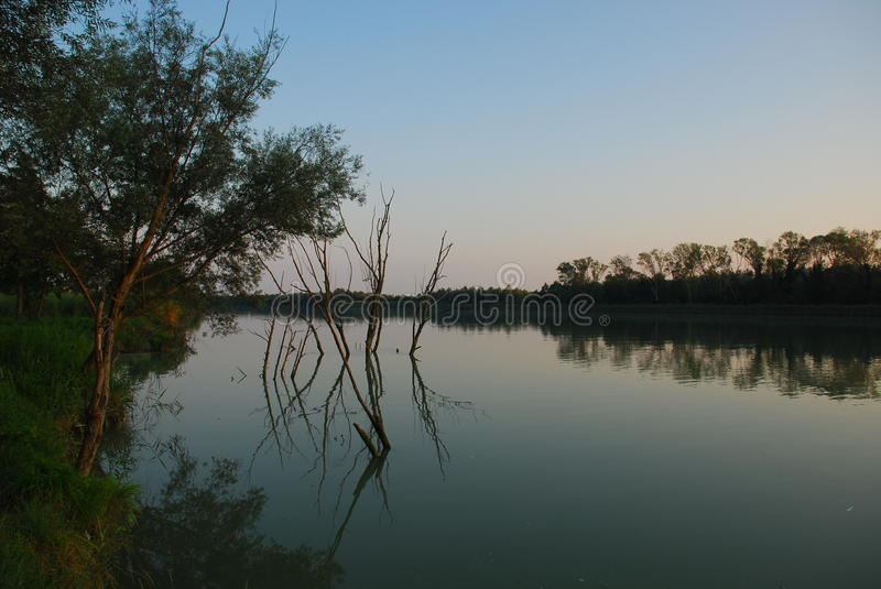 Dusk at River. The sun sets over a river in a wetland area in northern Italy royalty free stock images