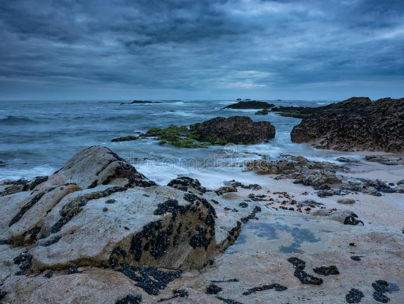Dusk on the rocky beach with dramatic clouds and dark moody sky. Long exposure. stock photo