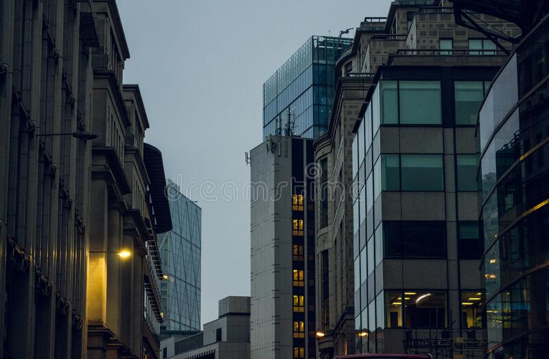 Dusk on a street with tall buildings royalty free stock images