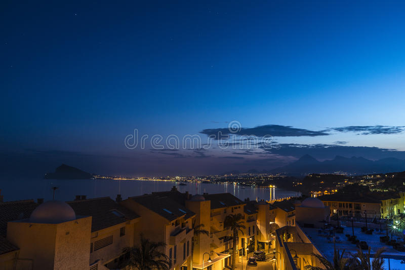 Dusk in the urbanization. Dusk from the urbanization with Benidorm in the background stock image