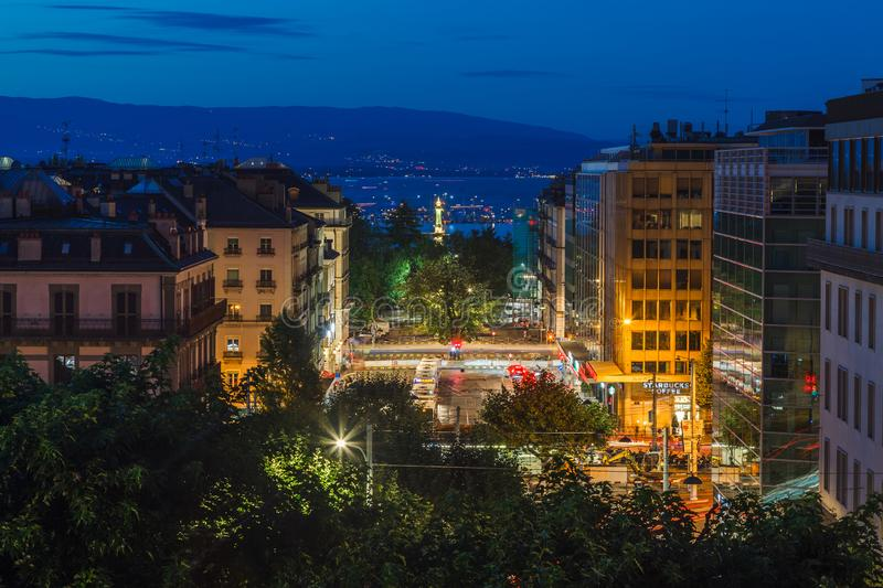 Dusk view of Geneva city streets with buildings, Geneva Lake Lac Leman and lighthouse during beautiful summer night, Geneva, royalty free stock photos