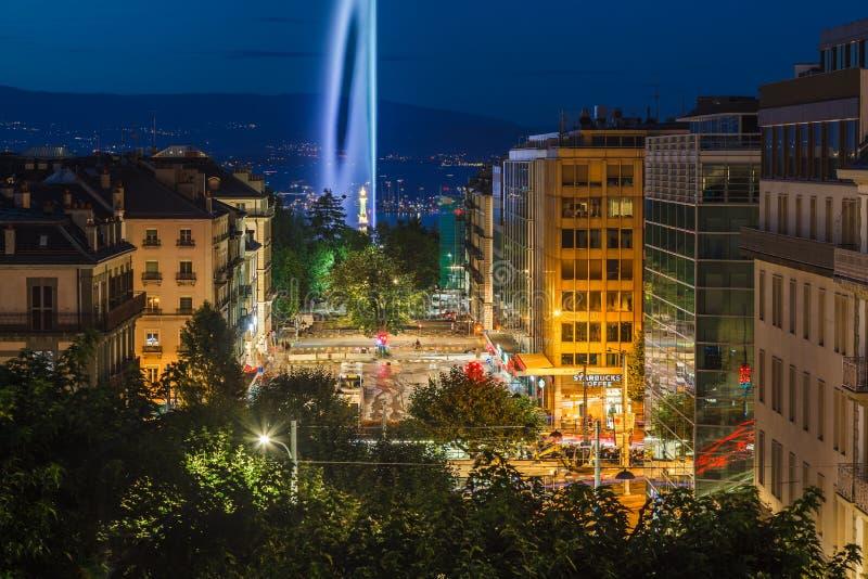 Dusk view of night city streets and illuminated landmark Geneva Water Fountain Jet d`Eau, Geneva, Switzerland royalty free stock photography