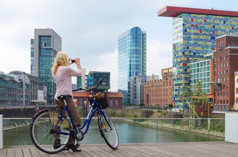 Dusseldorf, Duitsland - September 14, 2014: neemt de jonge vrouwen met citybike foto van gebouwen in media haven royalty-vrije stock afbeeldingen