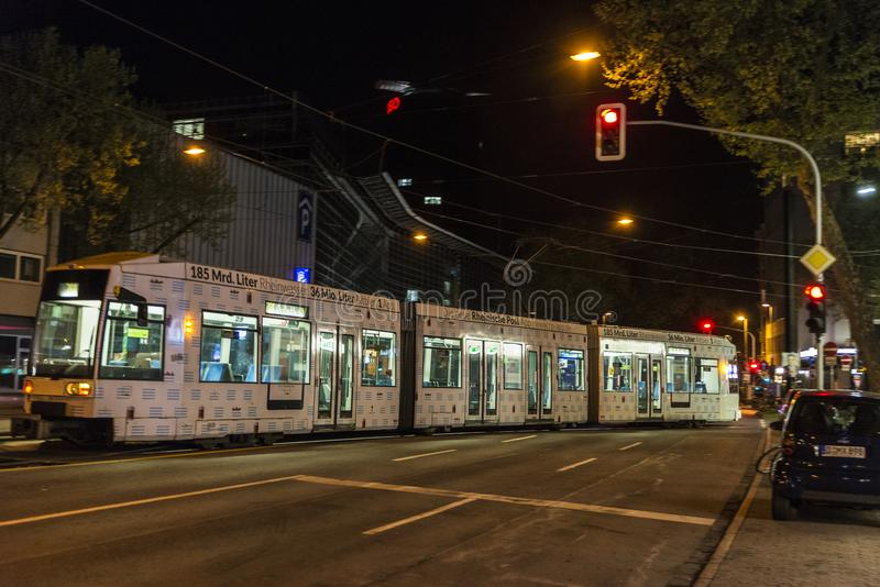 Tram at night in Dusseldorf, Germany. Dusseldorf, Germany - April 16, 2017: Tram with a street full of traffic lights in red at night in Dusseldorf, Germany on stock photos