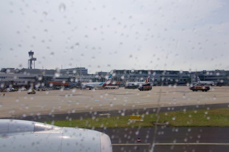DUSSELDORF - 22nd JULI 2016: flygplats som sett igenom ett flygplanfönster under regn arkivbild