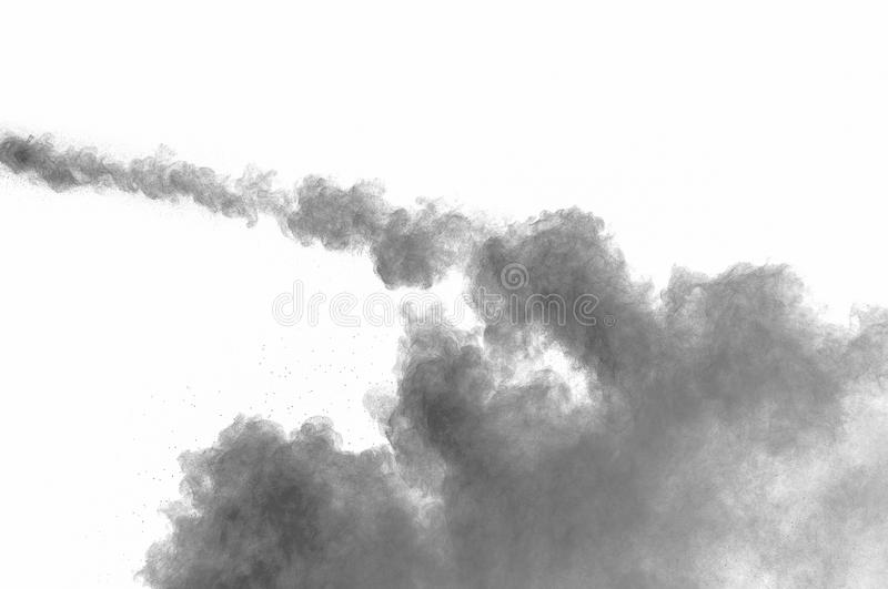 Dust explosion. Freeze motion of black dust explosion on white background. Stopping the movement of dark powder on white background. Explosive powder black on stock photography