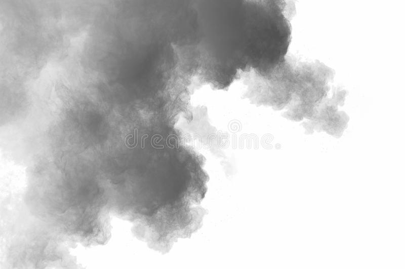 Dust explosion. Freeze motion of black dust explosion on white background. Stopping the movement of dark powder on white background. Explosive powder black on royalty free stock image