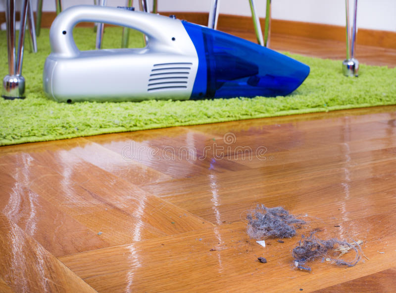 Dust on floor. House cleaning. Close up of dust on parquet floor in front of cordless vacuum cleaner. House keeping concept stock images