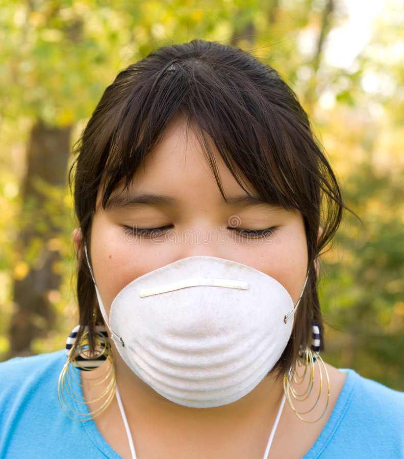Dust Mask. A nine year old girl wearing a dust mask outside royalty free stock photos