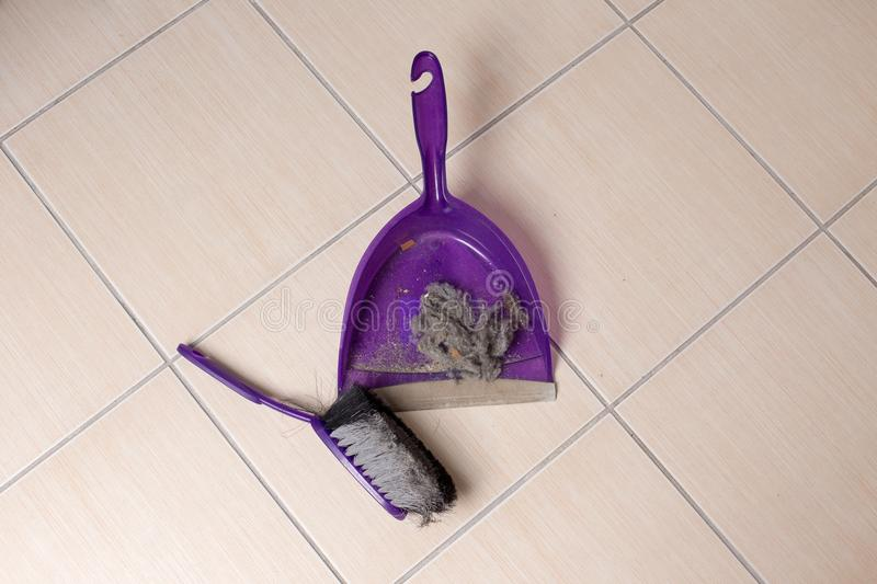 Dust pan with dirt on floor. Top view of dust pan full of dirt on tiled floor. Housekeeping concept royalty free stock photos