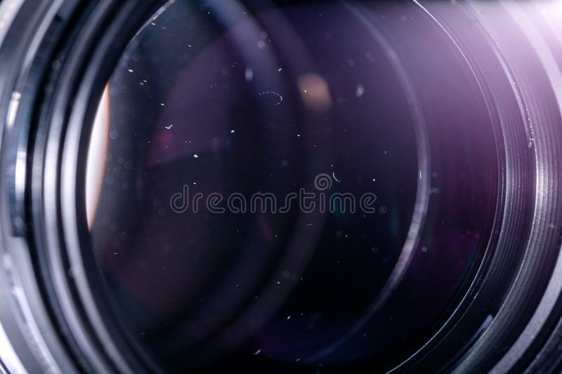 Dust particles in camera lens closeup shot with selective focus and blur. Large front element of professional objective royalty free stock photo