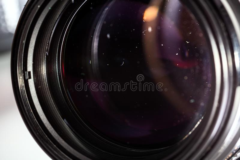 Dust particles inside camera lens closeup shot with selective focus and blur. Dust particles in camera lens closeup shot with selective focus and blur. Large stock photo