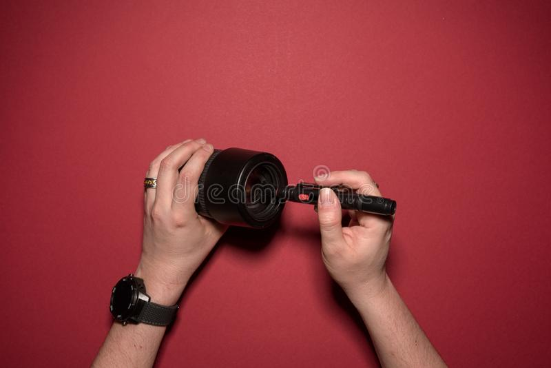 Man is cleaning a lense. Dust removel on a lense for a dsl camera royalty free stock photos