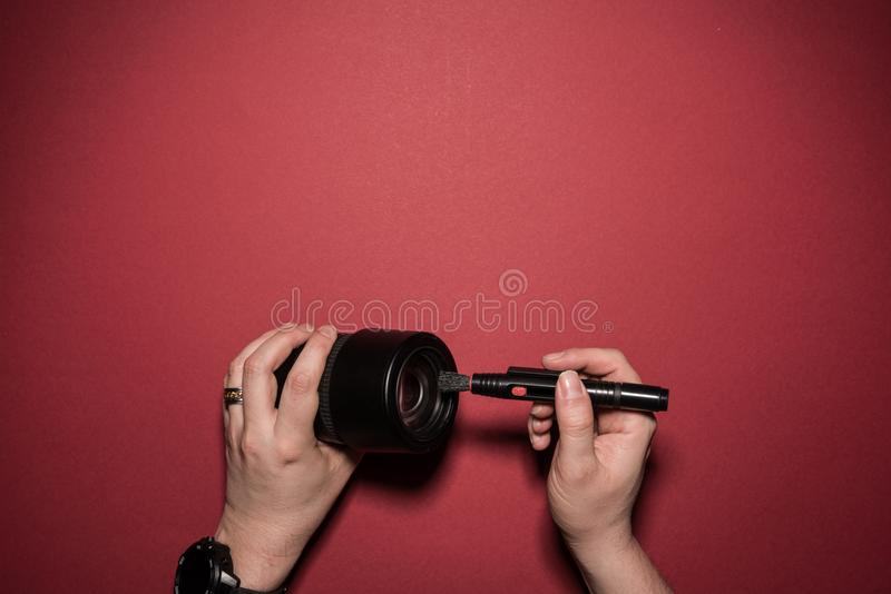 Man is cleaning a lense. Dust removel on a lense for a dsl camera royalty free stock image