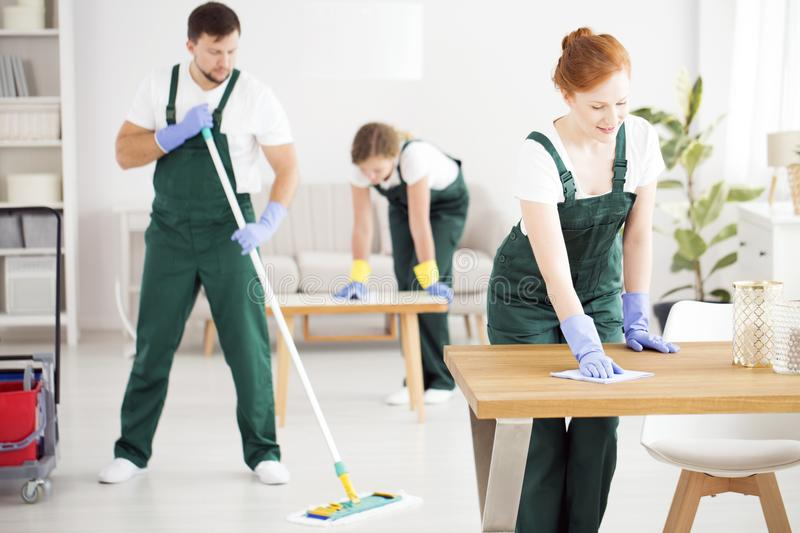 Dusting women and moping man. Two young women dusting tables and a men moping the floor in an apartment royalty free stock photo