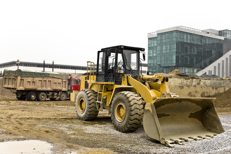 Dusty bulldozer parked on the construction site. Yellow and black dusty bulldozer parked on the construction site along with heavy truck stock image