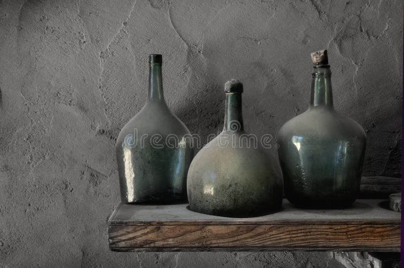 Dusty Cellar Bottles. Three old dusty wine bottles in a cellar with stucco walls stock photo