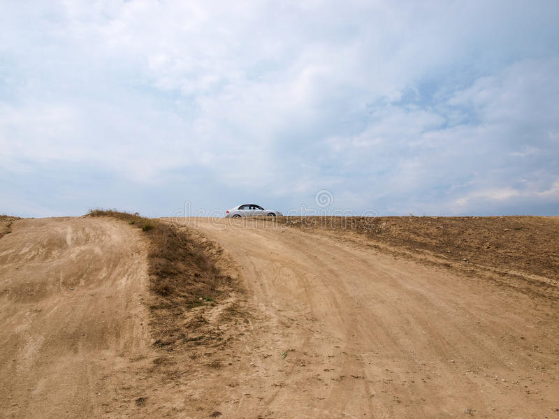 Dusty dirt road brought the car up the hill royalty free stock image