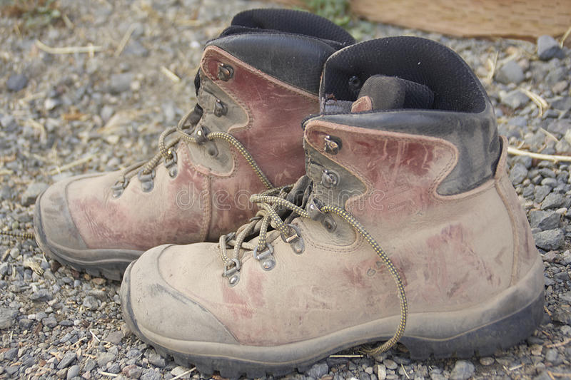 Dusty hiking boots. A pair of dusty hiking boots, sitting on gravel path royalty free stock photo