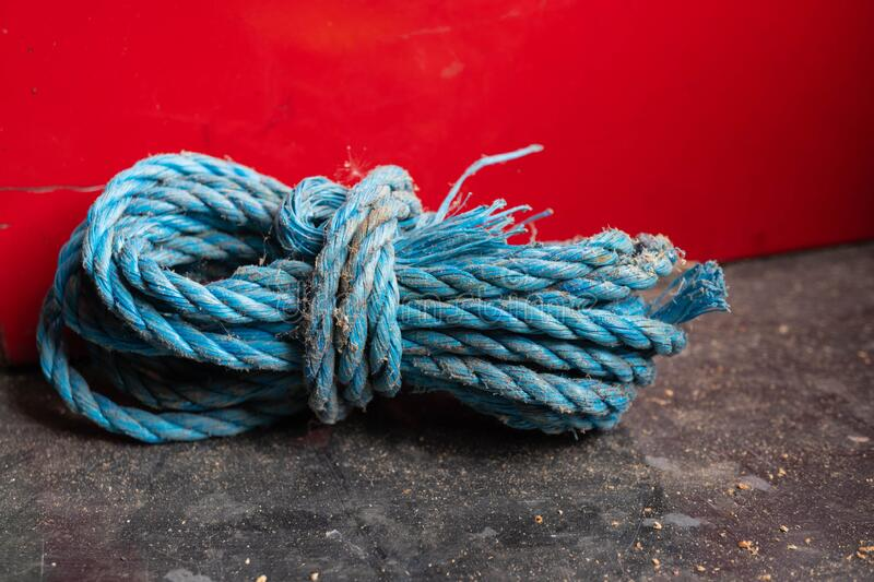 Dusty old bright blue rope against red background royalty free stock image
