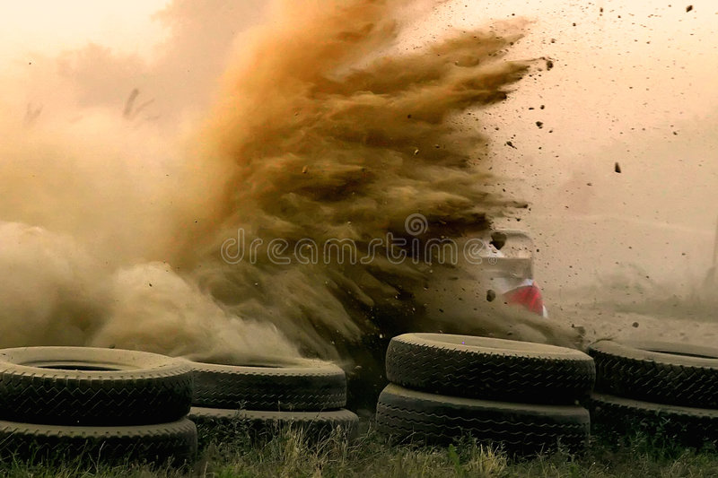 Dusty rally racing. Rally car passing by on gravel surface stock image
