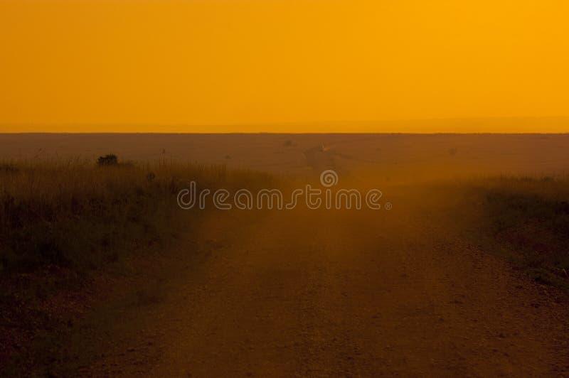 Dusty road into africa. Dusty road into samburu safari park at sunset royalty free stock photo