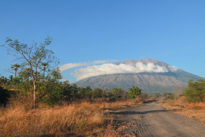 A dusty road to the foot of the volcano Gunung Agung on Bali Island in Indonesia illuminated by the rays of the rising sun. Long s stock photo