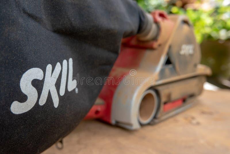 Dusty Skil-binnen maakt de merk elektrische schuurmachine tropisch hout glad royalty-vrije stock foto