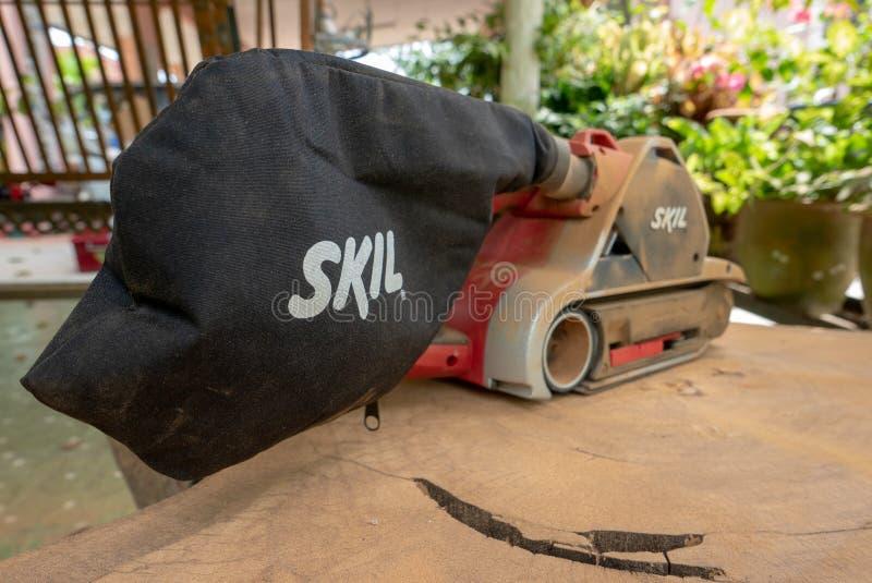 Dusty Skil-binnen maakt de merk elektrische schuurmachine tropisch hout glad royalty-vrije stock foto's