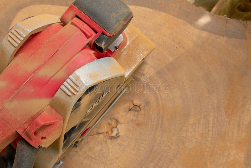 Dusty Skil-binnen maakt de merk elektrische schuurmachine tropisch hout glad stock foto
