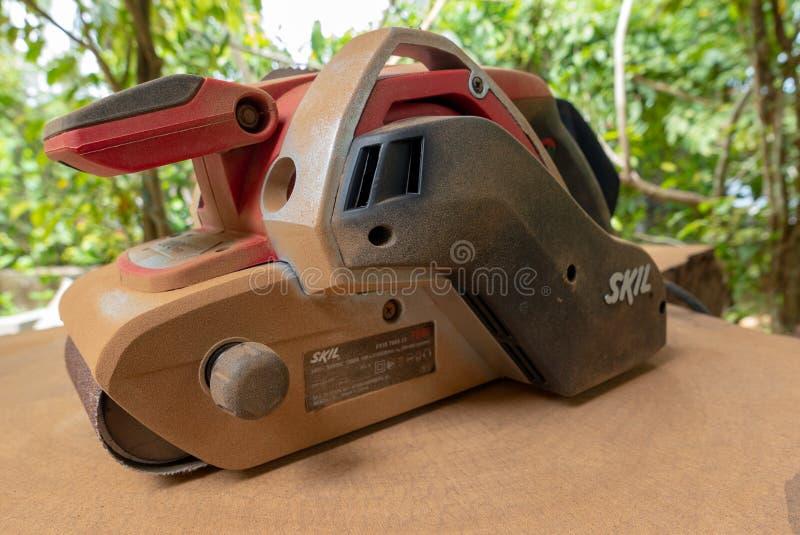 Dusty Skil-binnen maakt de merk elektrische schuurmachine tropisch hout glad stock fotografie